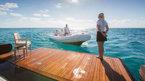 A stewardess standing on the swim platform of a yacht welcomes charter guests arriving by tender boat