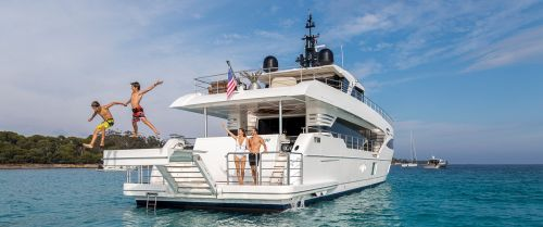 Two boys jumping from the swim platform of a boat during family yacht charter vacations
