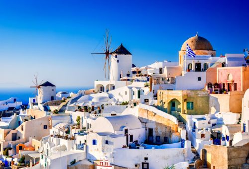 Fira, the capital of Santorini, with its whitewashed houses and mills under a beautiful blue sky