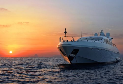 A luxury charter yacht at anchor at sunset