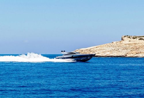 A sporty motor yacht cruising along the coast of Santorini