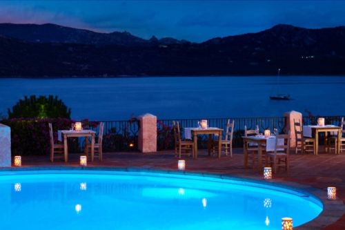 The pool of the Mira Luna restaurant with a view of the bay of Cannigione and some tables set up for dinner
