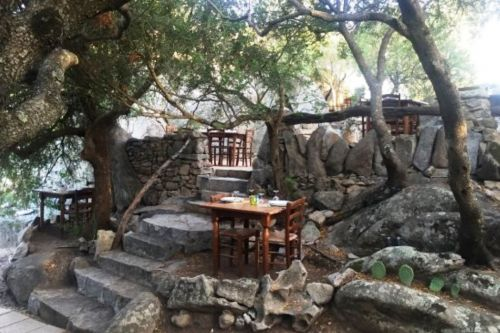 Tables set in a rocky garden at the traditional Pedristellas restaurant in Porto Rotondo