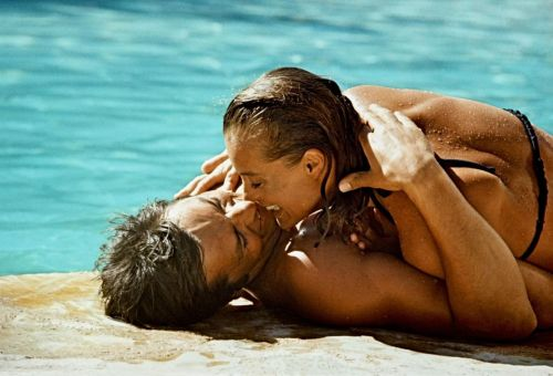 Romy Schneider and Alain Delon kissing near a pool in the movie The Swimming Pool