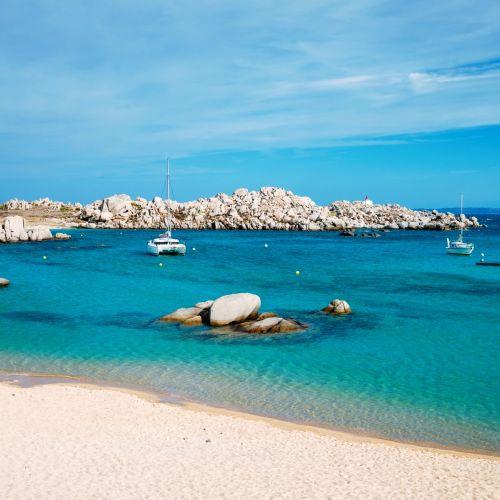 Cala Acciarino, the most beautiful beach of the Lavezzi Islands in Corsica, with a catamaran at anchor