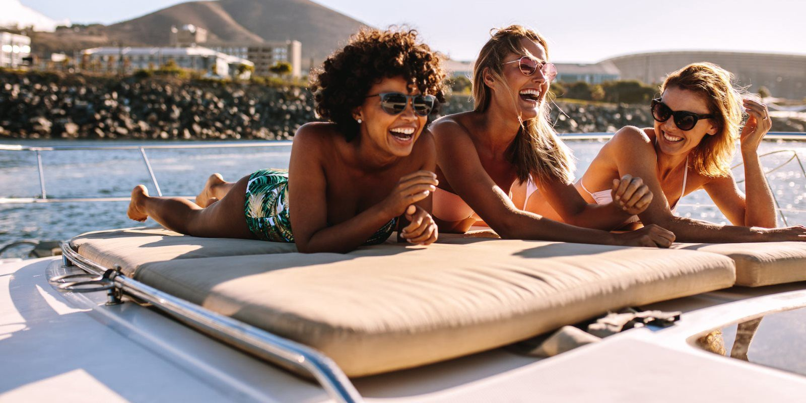 https://www.talamare.com/medias/Three girls enjoying a giggle on a yacht during a large group yacht rental
