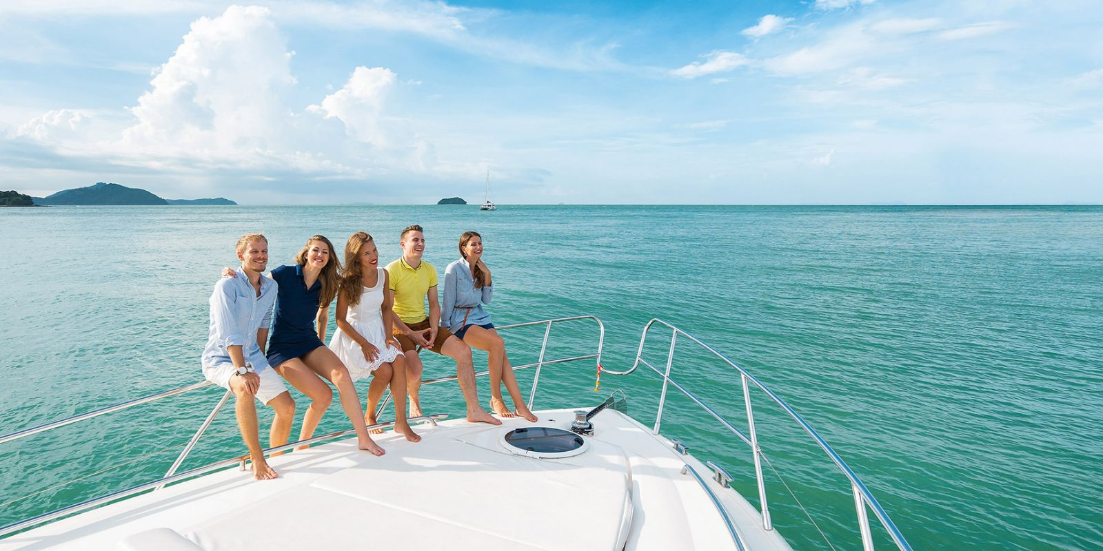 https://www.talamare.com/medias/A group of young people smiling on the bow of a motor yacht available for rental