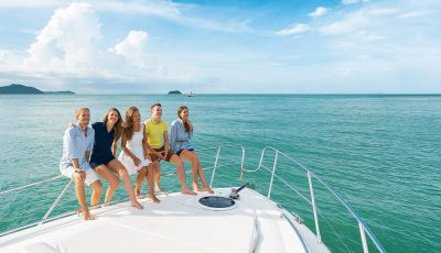 A group of young people smiling on the bow of a motor yacht available for rental