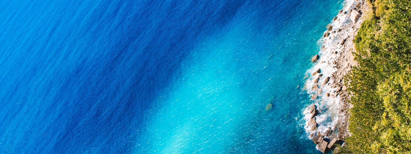 Aerial sea view with turquoise waters, pebbles beach and green vegetation