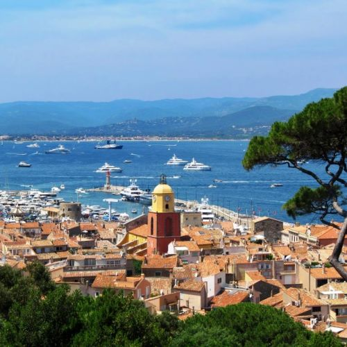 View of the village of St Tropez with its bell tower and charter yachts at anchor in the bay