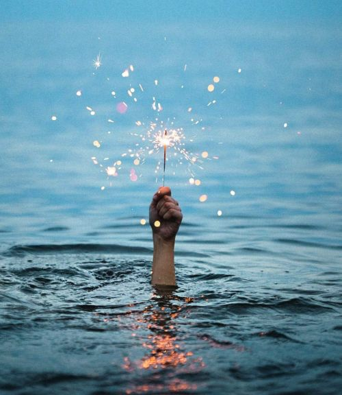 A hand holding sparklers in the sea