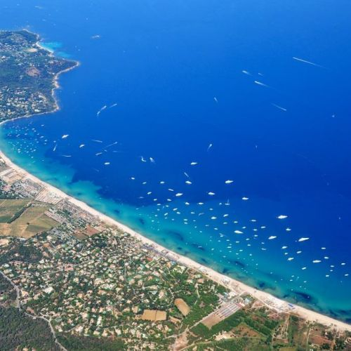 The beach of Pampelonne in Ramatuelle near St Tropez with its beach restaurants and charter yachts at anchor