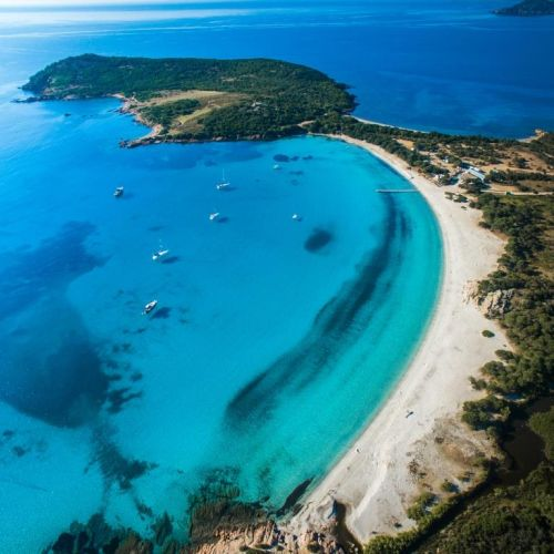 Aerial view of the gorgeous Rondinara beach in Corsica with charter yachts at anchor