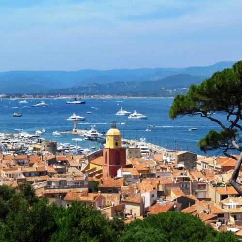 The village of St. Tropez with its beautiful bell tower and charter yachts at anchor in the bay