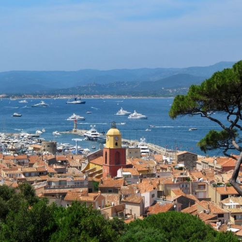 The village of St Tropez and its bell tower with yachts anchored in the bay