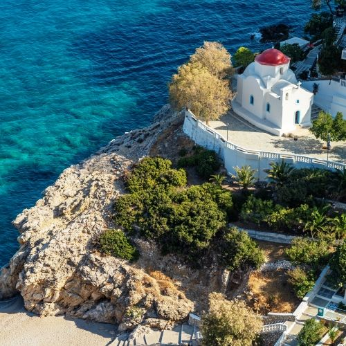 The beautiful monastery of Kyra Panagia with its red dome and the turquoise waters of the Mediterranean sea