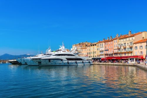 The port of St Tropez with the Café Sénéquier and moored charter yachts