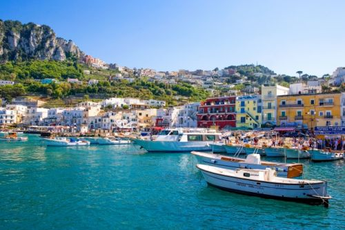The small port of Capri with its boats and colourful houses under a beautiful blue sky