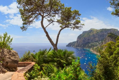 The coastal path of the island of Capri with a view of the Mediterranean sea and yachts at anchor
