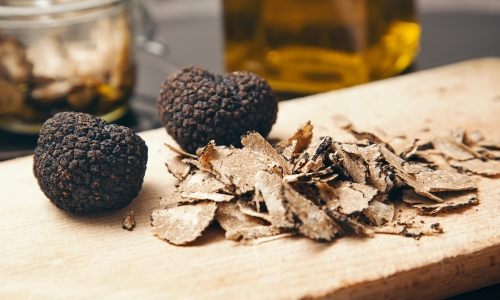 Two white truffles and shavings on an olive wood plank