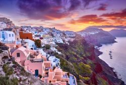 The village of Oia on the island of Santorini with a beautiful sunset and pink reflections on the houses