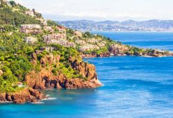 A bay in Théoule-sur-mer with the red rocks of the Esterel massif and the waters of the Mediterranean sea