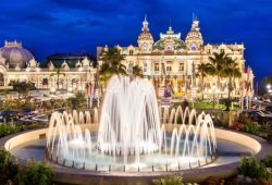 The casino of Monaco seen at night with its lights and a fountain on the square