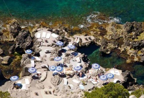 The beach restaurant La Fontelina in Capri with blue and white umbrellas, turquoise waters and people swimming