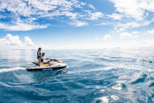 A couple using a jet-ski during their luxury yacht charter
