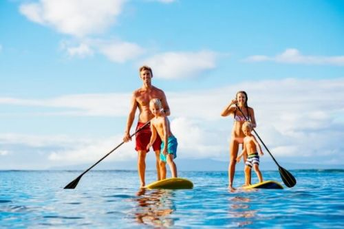 A family playing with paddle boards