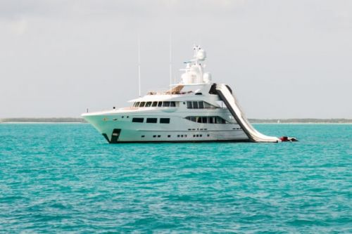 A luxury motor yacht at anchor with a waterslide from the top of the boat into the sea
