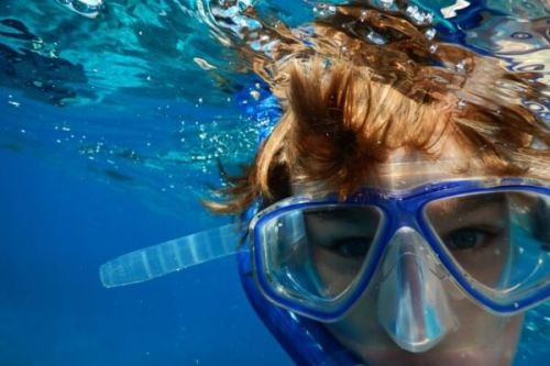 A boy snorkeling with mask and snorkel