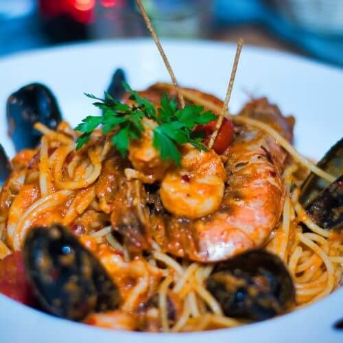 A plate of seafood pasta with mussels in a waterfront restaurant