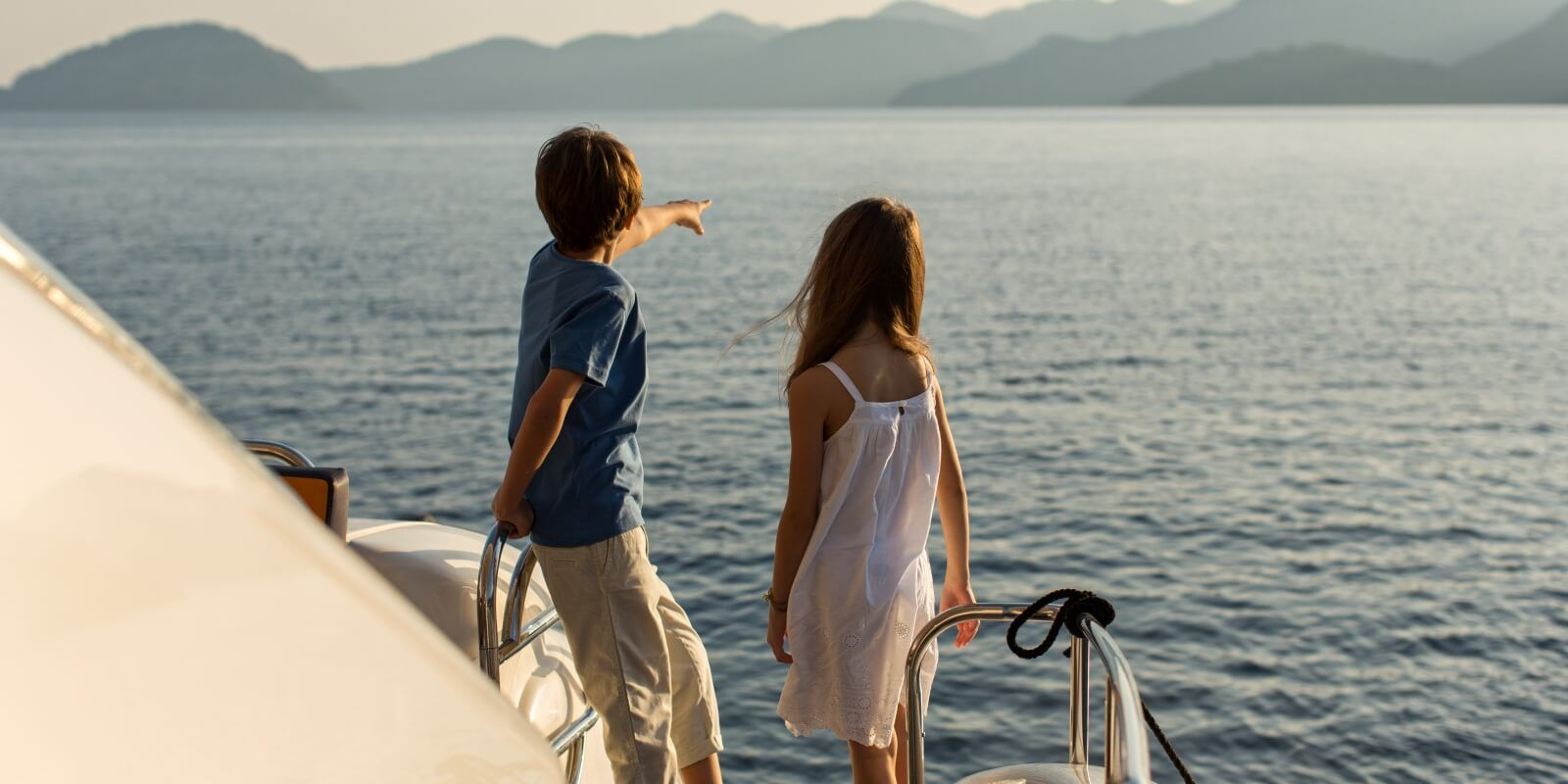 https://www.talamare.com/medias/Kids looking at the sea from a charter yacht with their parents on the aft deck