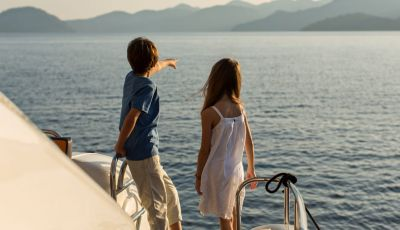 Kids looking at the sea from a charter yacht with their parents on the aft deck