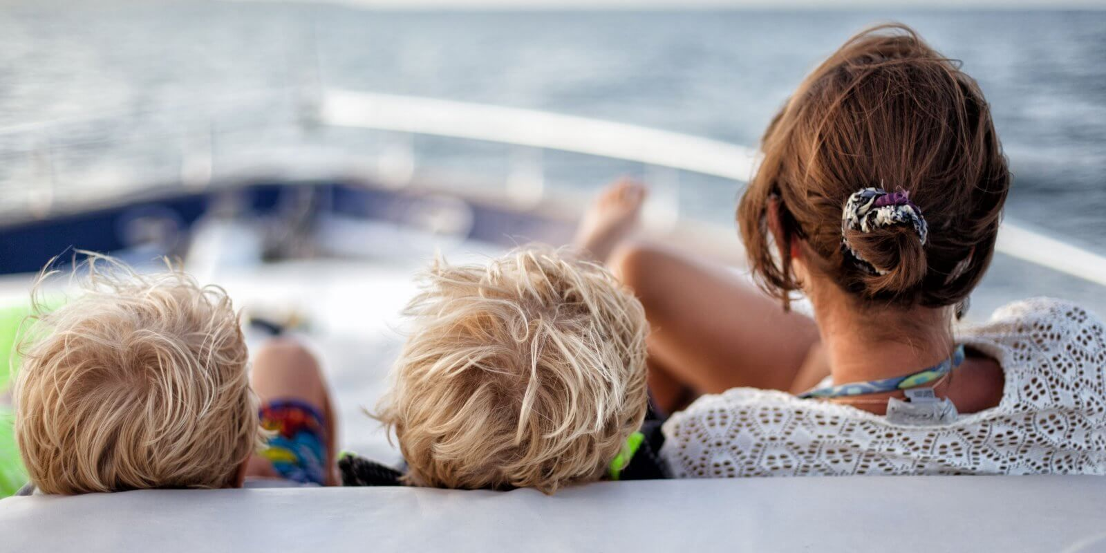 https://www.talamare.com/medias/A woman with kids relaxing on the foredeck sun pads of a family-friendly charter yacht