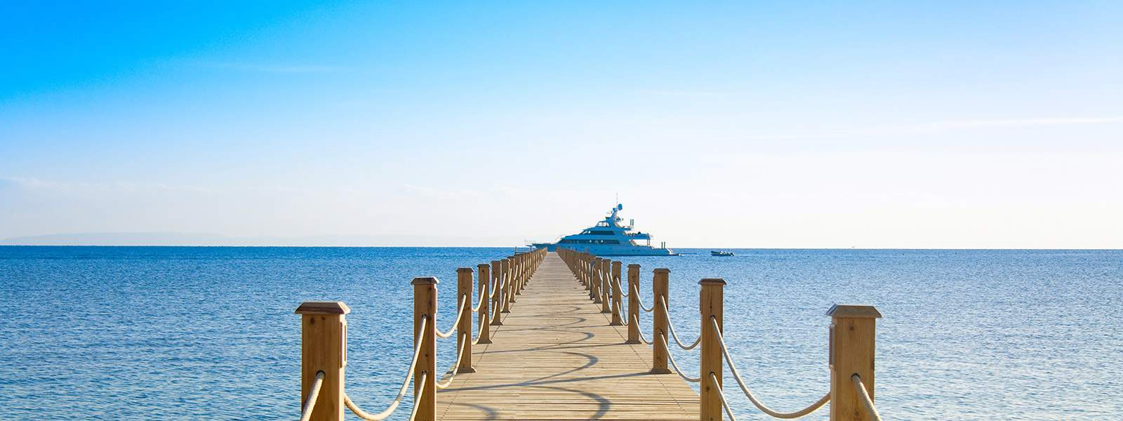 A wooden pontoon with a charter yacht ready to welcome charter guests