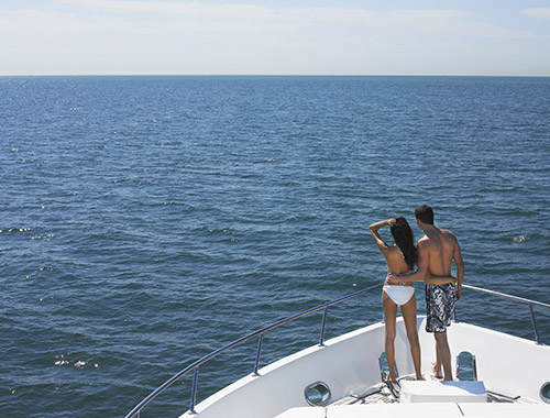 A couple in bathing suits standing at the bow of a charter yacht during their summer yachting holidays in the Mediterranean