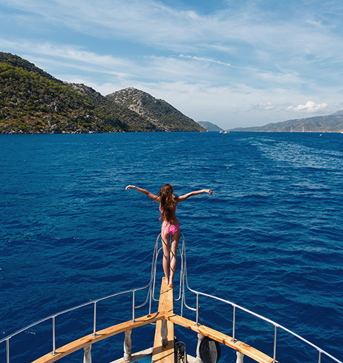 A woman in a bathing suit standing at the bow of a charter yacht in the Mediterranean