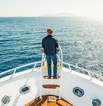 A yacht owner at the bow of his yacht gazing at the horizon
