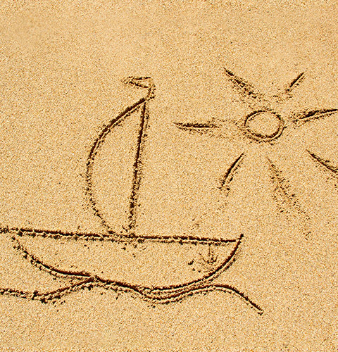 Hand drawing in the sand of a sailboat cruising on the water